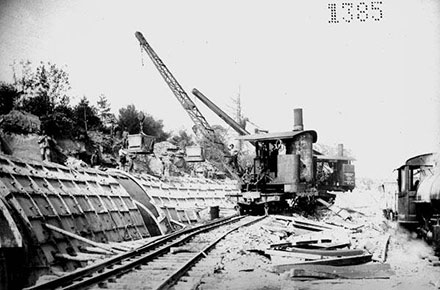 Using a hook rigged locomotive crane to pour concrete.