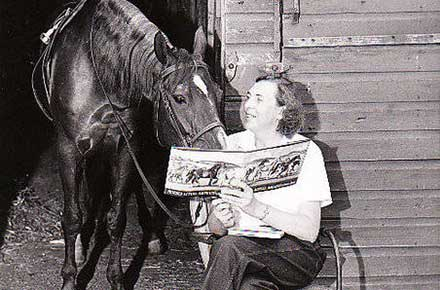 Ruth Douglas from the CCPL accounts department reads to a horse, 1958