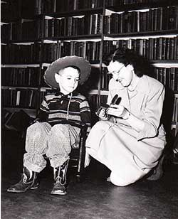 Librarian Frances Carman and little boy in cowboy clothes (1955?)