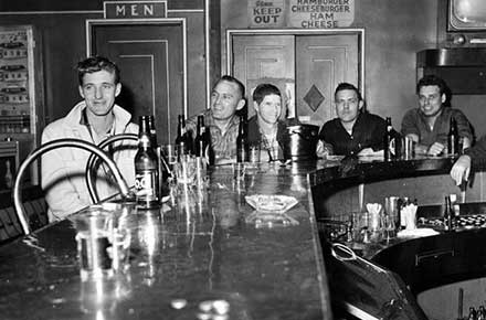 Patrons seated around a bar with a bottle of P.O.C. in the foreground