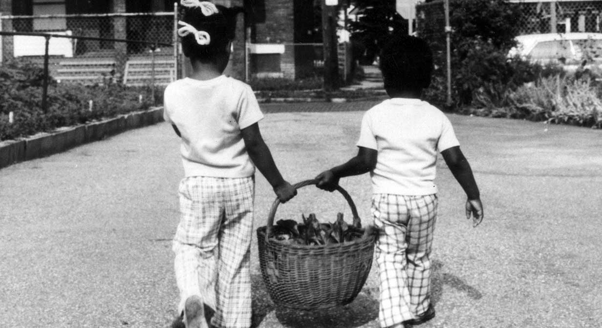 Two girls carr home a basket of garden greens.