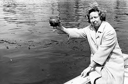 Betty Klaric holding water sample from Cuyahoga River.