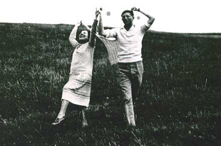 Authors Louis Bromfield and Edna Ferber hold hands and dance through a field of grass