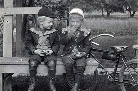 Two unidentified boys on bench, eating