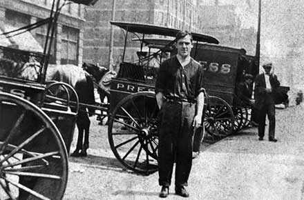 Man standing in front of Press's horse-drawn carriages.